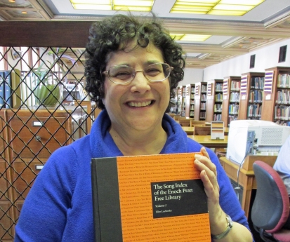 Ellie, holding with pride HER book, in the library she is so proud to work.